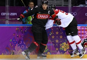 SOCHI, RUSSIA - FEBRUARY 14: Canada' Sidney Crosby #87 takes Austria's Matthias Trattnig #51 along the boards during men's preliminary round action at the Sochi 2014 Olympic Winter Games. (Photo by Jeff Vinnick/HHOF-IIHF Images)