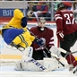 SOCHI, RUSSIA - FEBRUARY 15: Sweden's Daniel Sedin #22 goes airborne as Latvia's Arturs Kulda #32 trips him in front of the net as Kristers Gudlevskis #50 defends during men's preliminary round action at the Sochi 2014 Olympic Winter Games. (Photo by Andre Ringuette/HHOF-IIHF Images)